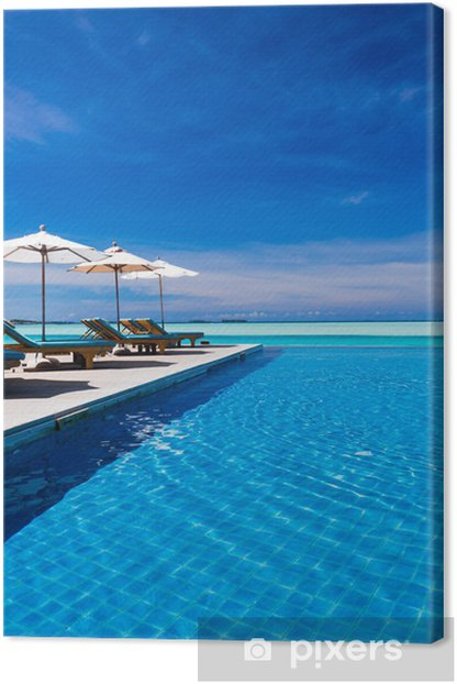 Deck chairs and infinity pool over amazing lagoon Canvas Print - Holidays