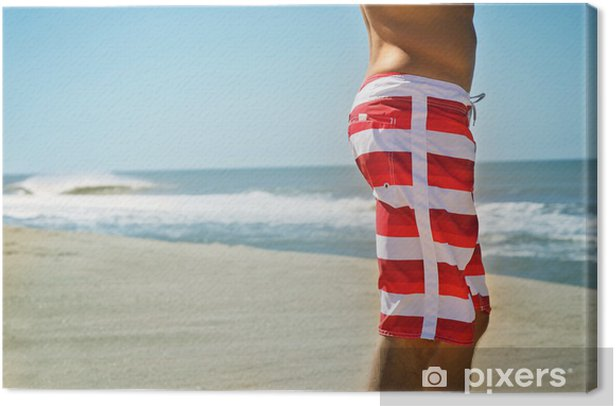 male surfer shorts standing on the beach wave in background Canvas Print - Holidays