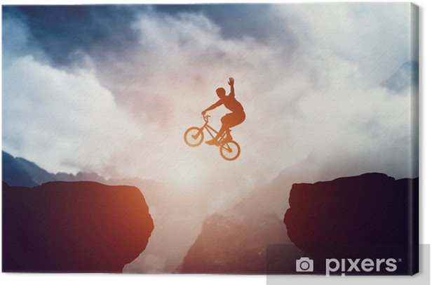 Man jumping on bmx bike over precipice in mountains at sunset. Canvas Print - Sports