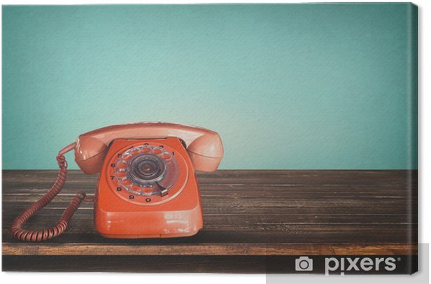 Old retro red telephone on table with vintage green pastel background Canvas Print -