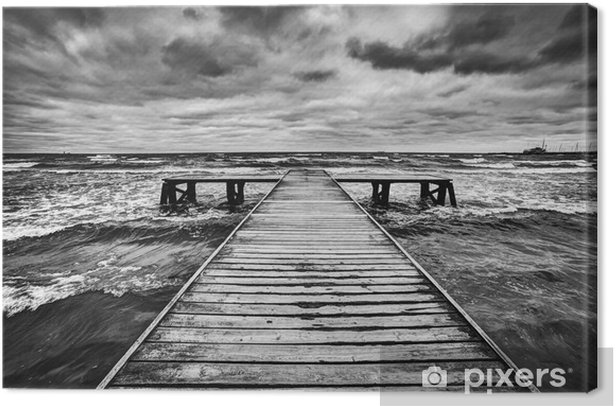 Old wooden jetty during storm on the sea. Dramatic sky Canvas Print -