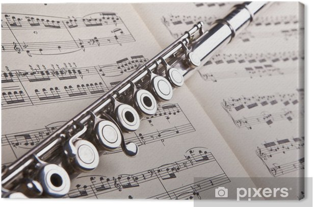 Silver flute on an ancient music score background Canvas Print - Music