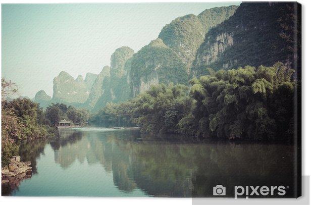 Canvas Schilderachtig uitzicht op yulong rivier tussen groene bossen en karst bergen op yangshuo county van guilin, China. yangshuo is een populaire toeristenbestemming van Azië. - Landschappen