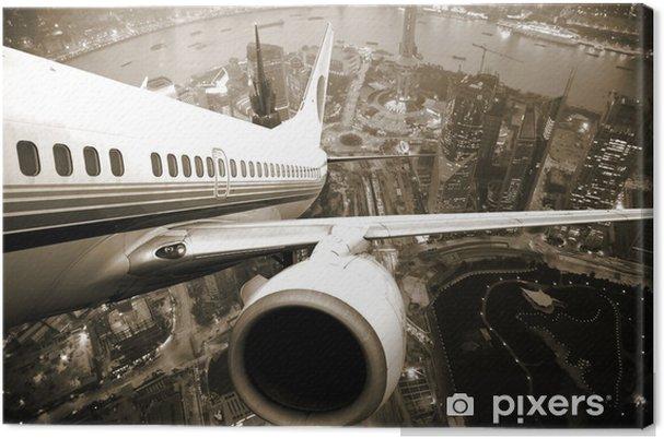 Canvas Vertrekkend vliegtuig boven de stad -