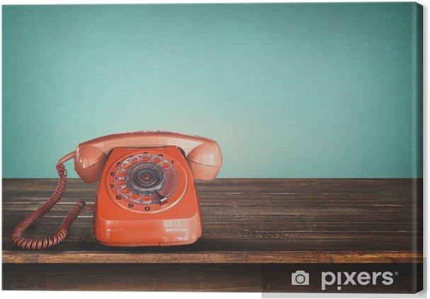 Canvastavla Retro röd telefon på bordet med vintage grön pastellfärgad bakgrund -