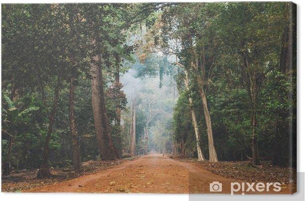 Cuadro en Lienzo Camino de tierra que se extiende a través de la selva de Camboya. - Paisajes