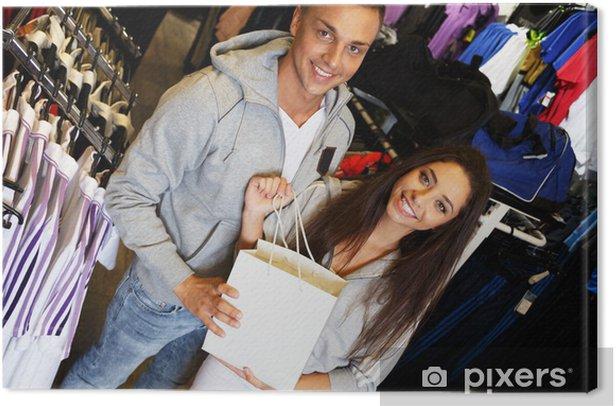 Cuadro en Lienzo Feliz pareja joven con bolsa de la compra en la tienda de ropa deportiva - Moda
