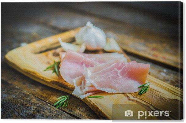 Cuadro en Lienzo Prosciutto con ajo y romero en el fondo de madera rústica - Temas