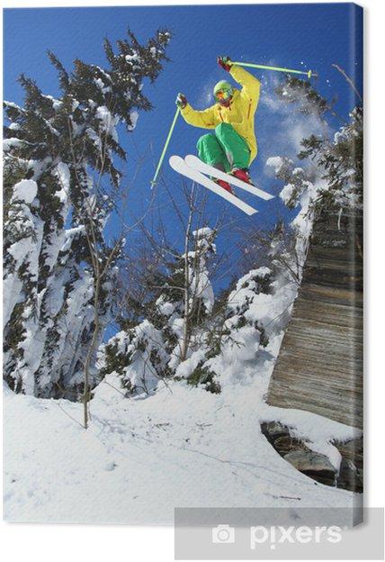 Leinwandbild Coole Skifahrer springt gegen den blauen Himmel aus dem Felsen - Skisport
