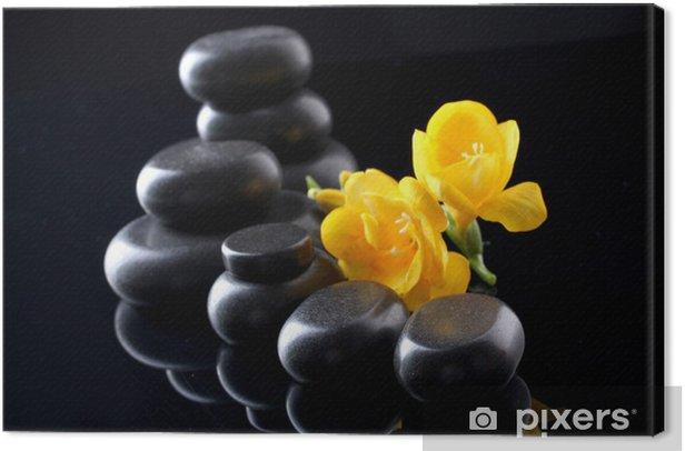 Leinwandbild Spa Steine und gelbe Blume auf schwarzem Hintergrund -
