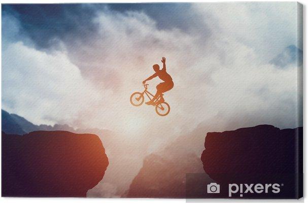 Obraz na płótnie Człowiek skoki na rowerze bmx nad przepaścią w górach na zachód słońca. - Sport