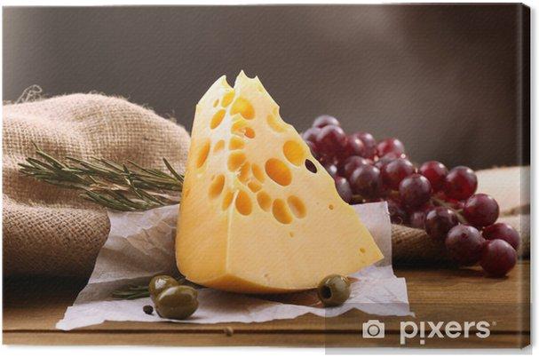 Obraz na płótnie Kawałek sera na tabliczce z zielonych oliwek, na drewnianych - Sery