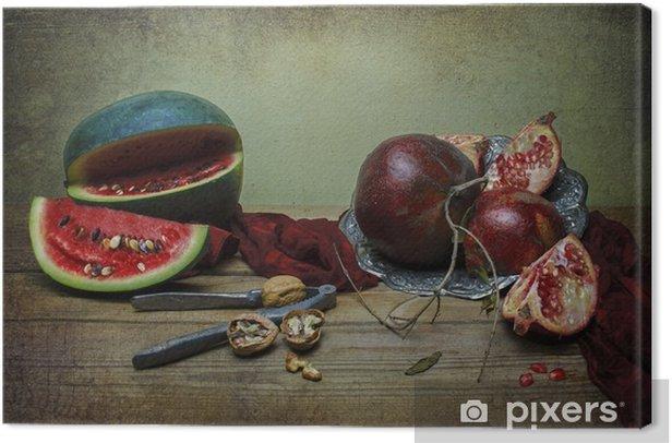 Obraz na płótnie Klasyczna martwa natura z arbuzem i granatu umieszczone w klasycznym srebrnym talerzu z czerwonym szalikiem, jedwabistej jakiegoś orzechowego i orzeszków kruszarki na wiejskim drewnianym stole. - Jedzenie