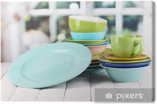 Obraz na płótnie Kolorowe naczynia na drewnianym stole na tle okna - Tematy