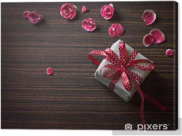Obraz na płótnie Pudełko na drewnianym stole z płatkami róż, wstążki zakrzywione. - Szczęście
