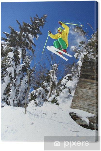 Obraz na płótnie Spoko narciarz skacząc z błękitnego nieba ze skały - Narciarstwo