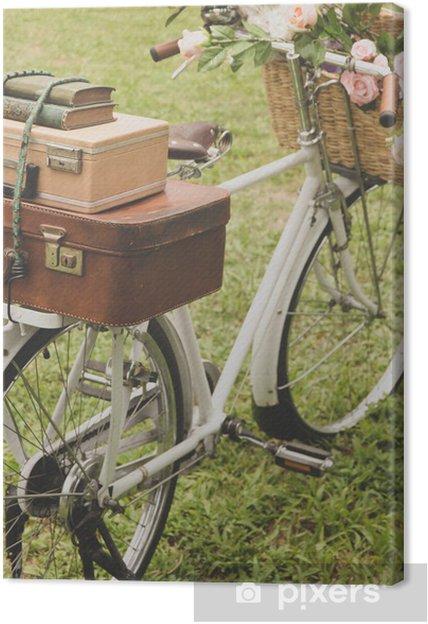 Obraz na płótnie Vintage rower na polu z koszem kwiatów - Rowery