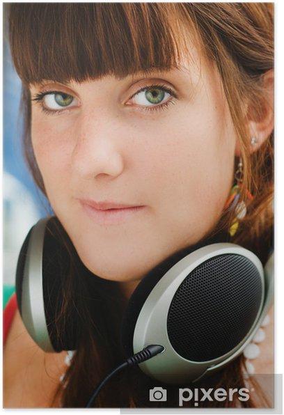 Plakat Dość młoda dziewczyna z wielkimi słuchawkami do słuchania muzyki - Kobiety