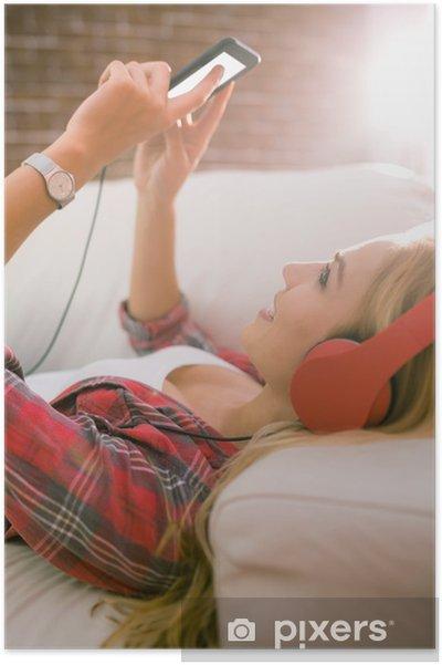 Plakát Hezká blondýnka poslouchá hudbu na gauči - Lidé