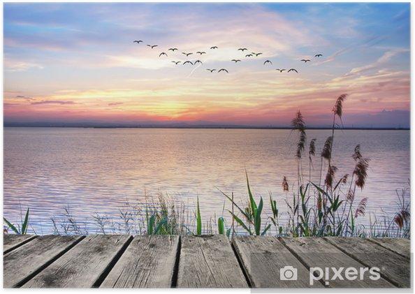 Plakat samoprzylepny Drewniany pomost na tle zachodzącego słońca -