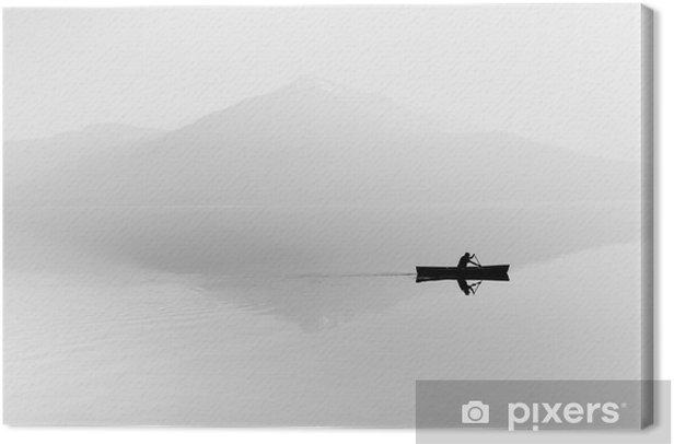 Quadro su Tela Nebbia sul lago. Silhouette di montagne sullo sfondo. L'uomo galleggia in una barca con una pagaia. Bianco e nero - Hobby e Tempo Libero