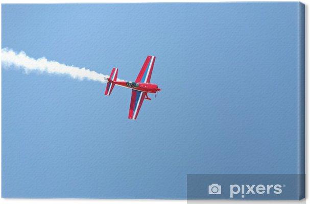 Tableau sur toile Acrobaties aériennes - avion à hélice rouge avec de la fumée bleue ciel - Thèmes
