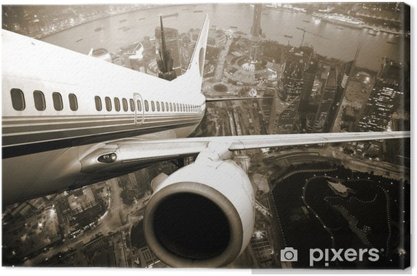 Tableau sur toile Avion en plein décollage quittant la ville -