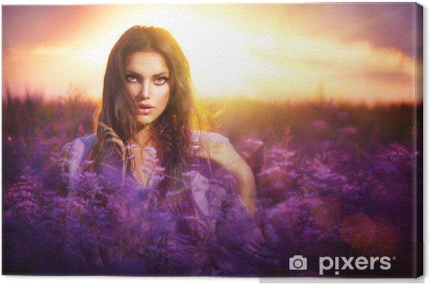 Tableau sur toile Beauté fille se trouvant sur un pré avec des fleurs violet - Femmes