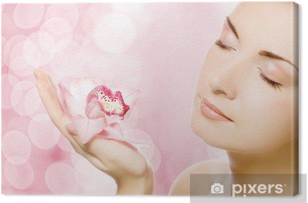 Tableau sur toile Belle jeune femme avec orchidée rose - Beauté et soins du corps