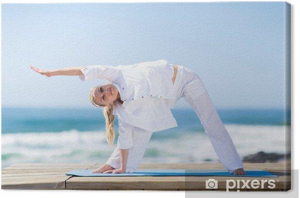 Tableau sur toile Femme aîné s'exerçant sur la plage - Pour école de yoga