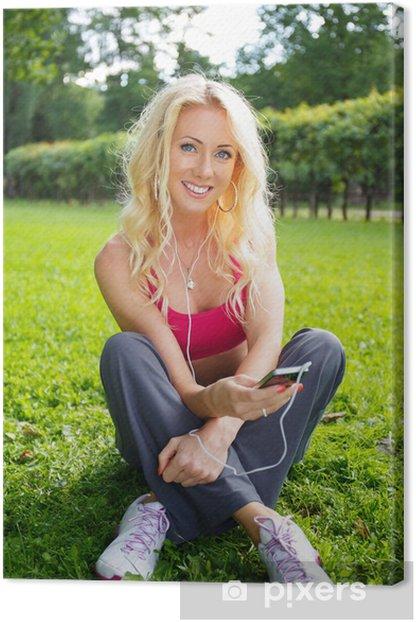 Tableau sur toile Jeune fille blonde souriante athlétique assis sur l'herbe - Autres