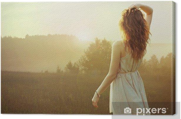Tableau sur toile Jolie femme brune en regardant le coucher du soleil - Femmes