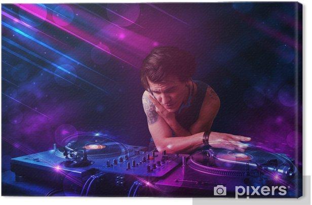 Tableau sur toile Le jeune DJ jouant sur les platines avec des effets de lumière de couleur - Divertissements