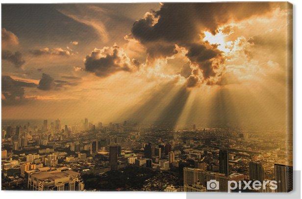 Tableau sur toile Les rayons de lumière qui brille à travers les nuages sombres avec la ville ci-dessous - Thèmes
