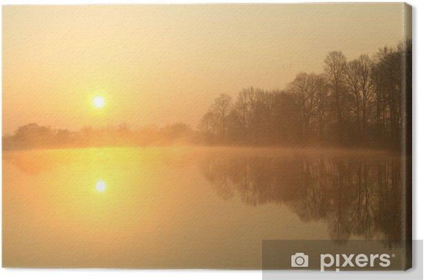 Tableau sur toile Lever de soleil sur le lac avec le reflet des arbres nus dans l'eau - Ciel
