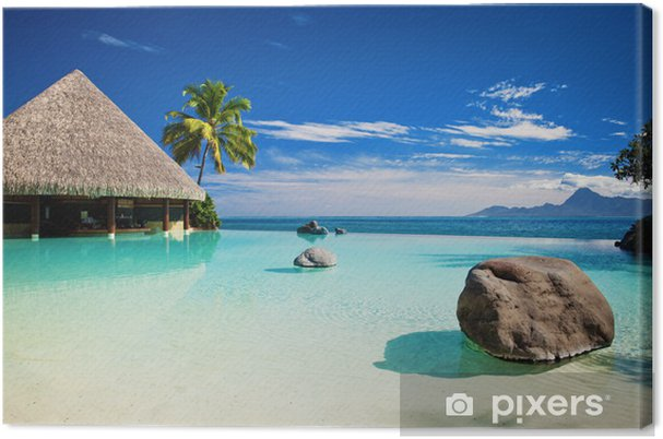 Tableau sur toile Piscine à débordement avec plage artificielle et l'océan - Palmiers