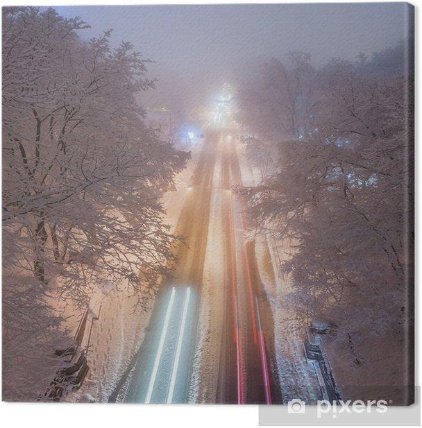 Tableau sur toile Tempête de neige, routes glissantes et beaucoup de trafic dans la ville de nuit - Infrastructures