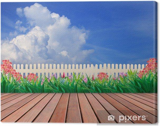 Tableau sur toile Terrasse en bois et jardin fleuri avec fond de ciel bleu