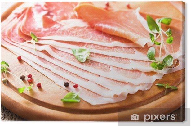 Tableau sur toile Tranches de jambon prosciutto sur planche à découper avec de l'origan et le poivre - Thèmes