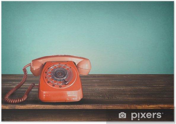 Zelfklevende Poster Oude retro rode telefoon op tafel met vintage groene pastel achtergrond -