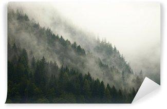 Afwasbaar Fotobehang Bomen op een berg in de mist