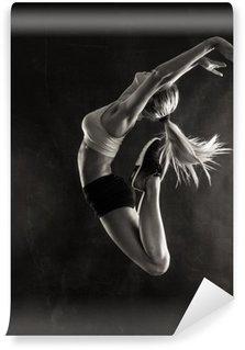 Afwasbaar Fotobehang Fitness vrouwelijke vrouw met een gespierd lichaam springen.