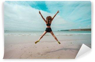 Afwasbaar Fotobehang Jonge vrouw doet star springt op het strand