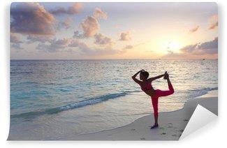 Afwasbaar Fotobehang Vrouw die zich uitstrekt op het strand