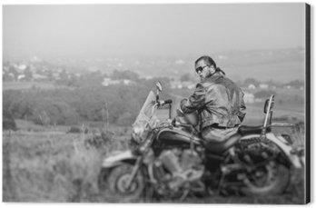 Aluminiumtavla Brutal cyklist med skägg bär skinnjacka och solglasögon sitter på sin motorcykel på en solig dag, håller hjälmen. Horisontell bild. Bakåtsikt. Tilt shift effekt linsoskärpa. Svartvitt