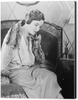 Aluminiumtavla Ung kvinna sitter på sin säng i sovrummet, talar i telefon