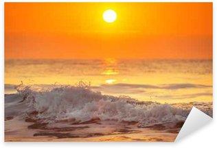 Autocolante Pixerstick Nascer do sol e as ondas que brilham no oceano