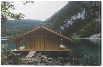 Canvas Houten huis op meer met bergen en bomen