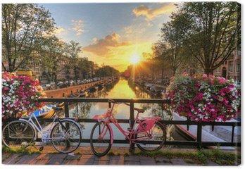 Canvas Mooie zonsopgang over Amsterdam, Nederland, met bloemen en fietsen op de brug in het voorjaar
