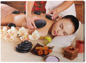 Adult woman having hot stone massage in spa salon Canvas Print